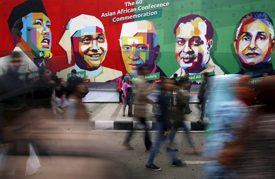 People walk in front a poster of prominent attendees of the 1955 Asian-African Conference on Asia Afrika street in Bandung, Indonesia, April 24, 2015. Leaders of Asian and African nations attended a commemoration ceremony on Friday marking 60 years since the commemoration of the Asian-African Conference.  REUTERS/Beawiharta