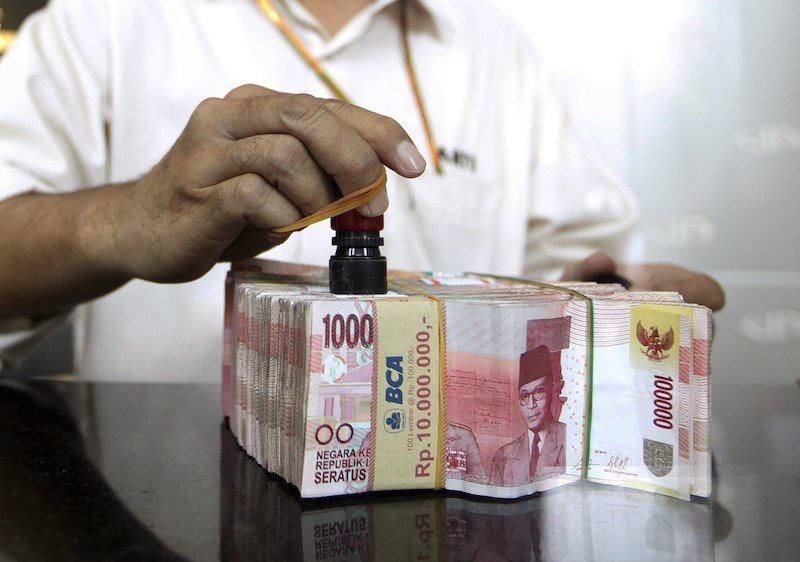 A money changer employee puts a stamp on Indonesia rupiah in Jakarta, September 29, 2015. Indonesian government officials on Tuesday announced a series of new economic stimulus measures, the second such package in three weeks, to help prop up the battered rupiah and revive growth in Southeast Asia's largest economy.  REUTERS/Nyimas Laula