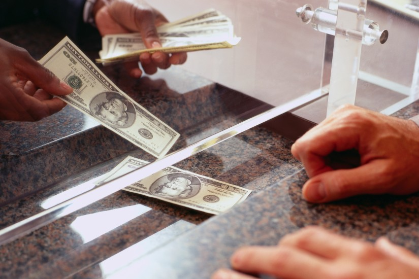 Bank Teller Counting Money for Customer --- Image by © Duncan Smith/Corbis